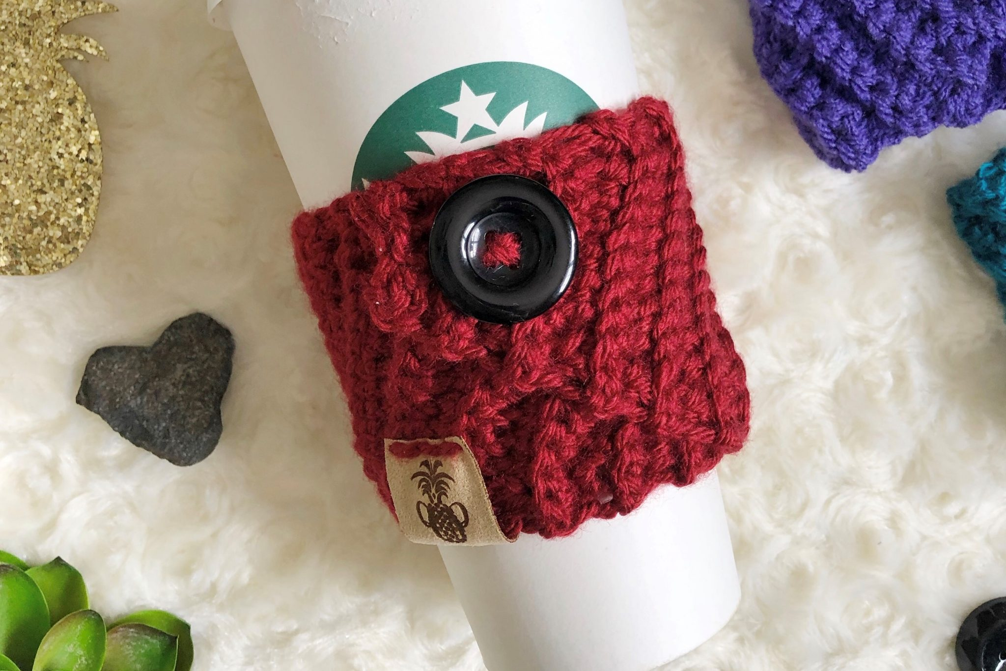 A crochet coffee cozy made with the Kelsi Cozy crochet pattern in red with large black button