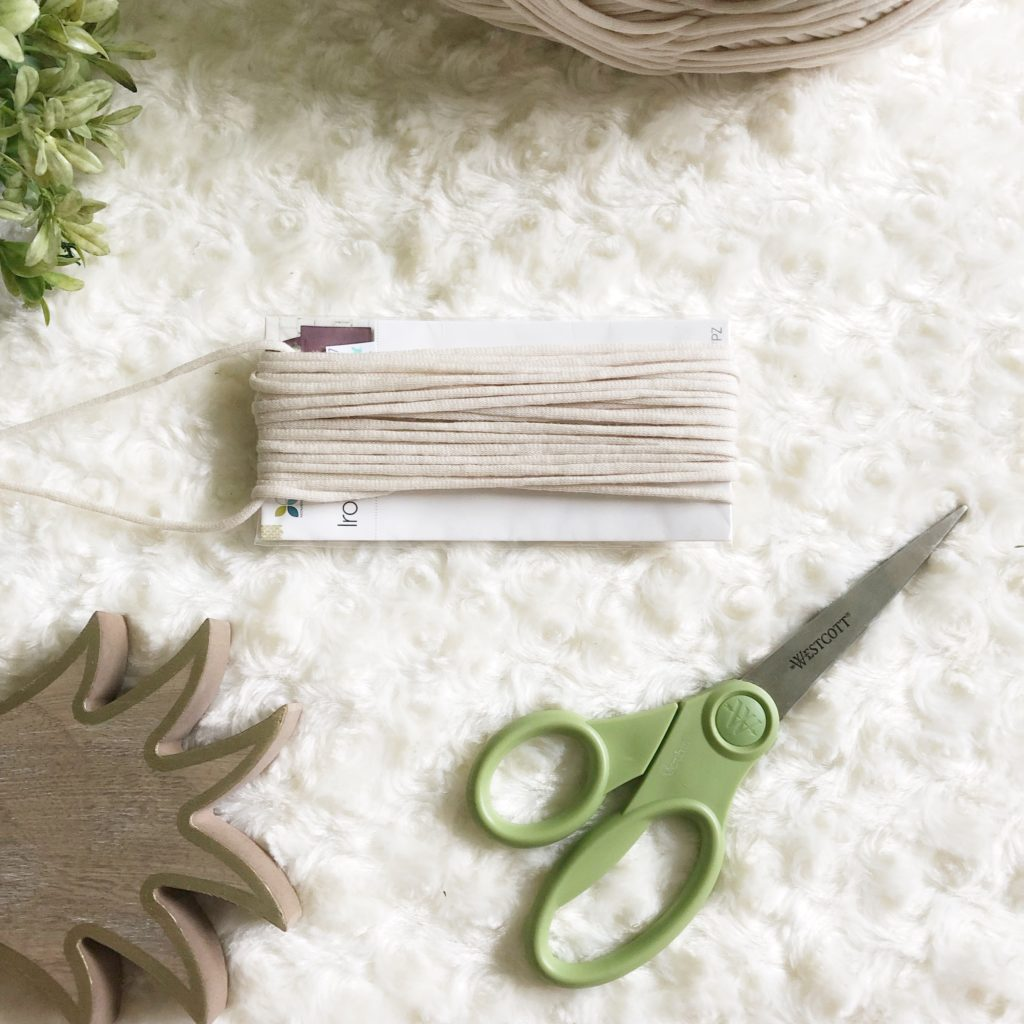 Close up of how to thread a piece of yarn under loops to form a tassel