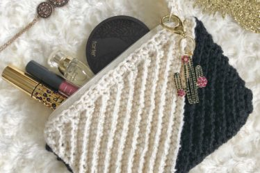 Black and white crochet clutch made with the Kelsi Clutch pattern with a cactus keyring and filled with makeup