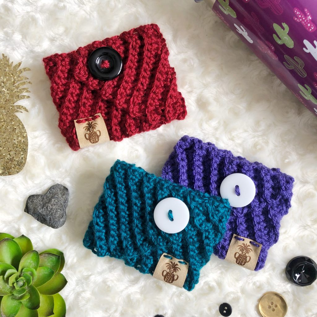 Crochet coffee cozies in red, green, and purple made from the Kelsi Cozy pattern by Sarah | The Plush Pineapple