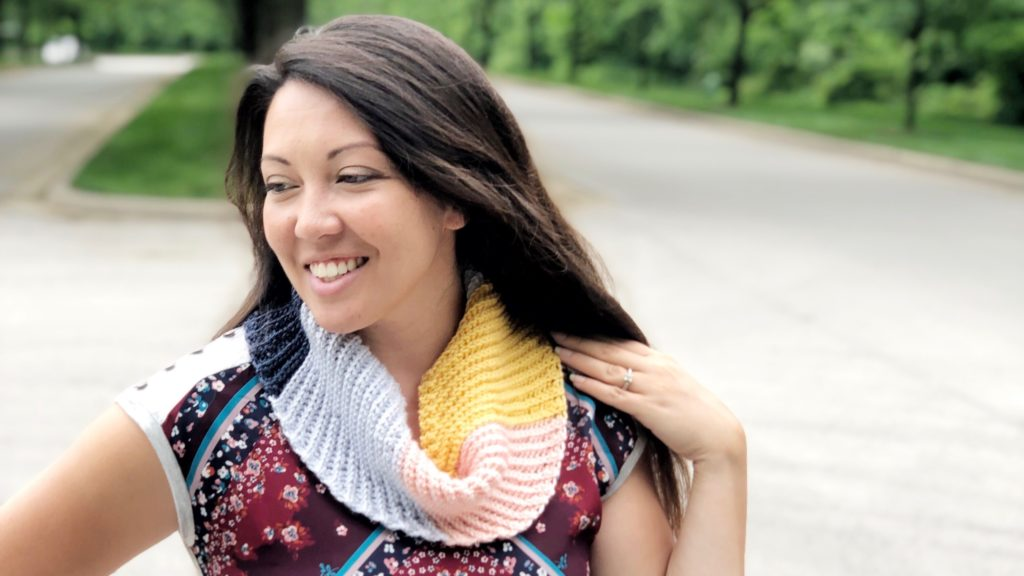 Multicolored crochet scarf with diagonally ribbed texture made with the Kelsi Scarf pattern shown in use.