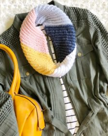 Multicolored crochet scarf with diagonally ribbed texture made with the Kelsi Scarf pattern shown in flat lay.