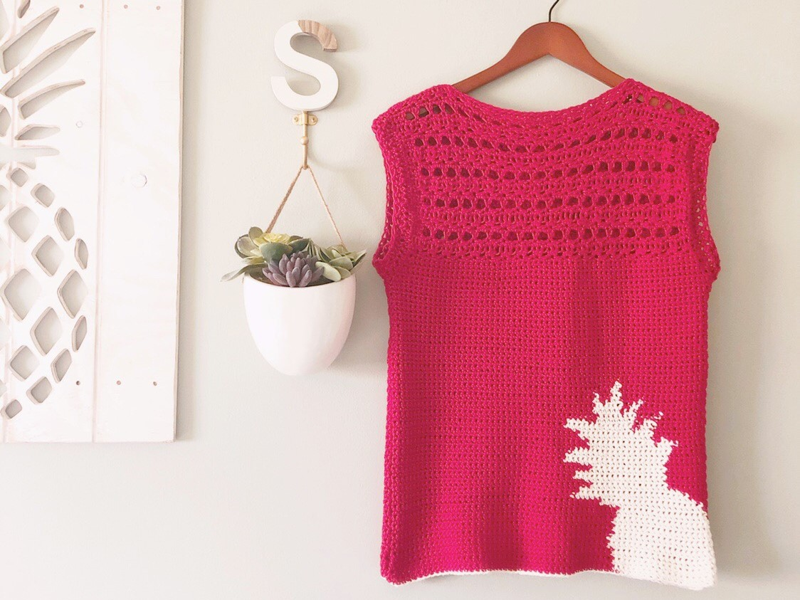 Red crochet top with cream pineapple color work in the bottom right corner with a lacy, open yoke and cap sleeves shown in size small