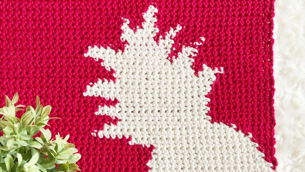 Red crochet panel with cream pineapple color work in the bottom right corner