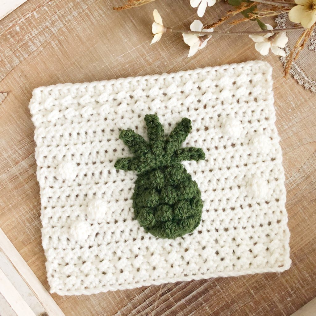 An off-white crochet square that is part of a blanket CAL with a dark green crochet pineapple applique sitting atop a neutral background accented by white flowers and coffee mug.